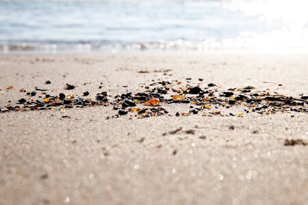 Amber stones by the sea on golden sand on a sunny day. Stock Photo