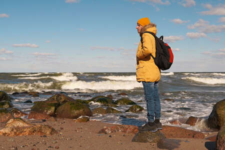 A man in a yellow jacket and hat with a large backpack on the seashore leaned on a large stone and looks into the distance. Traveling in Europe, a world without borders.