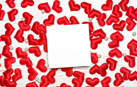 Many small red hearts on a wooden background. With a place for congratulations on a holiday. View from above.