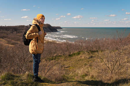 A man in a yellow jacket and hat with a large backpack on the side of the mountain looks into the distance to the sea. Traveling in Europe, a world without borders. Foto de archivo