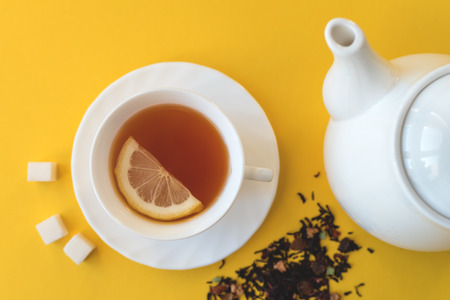 Kettle and a cup of tea with lemon and sugar on a yellow background fletley.
