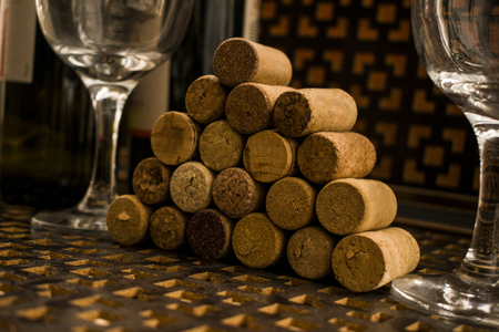 Cork from a wine bottle. folded ladder. Next to the wine glasses. On a brown background