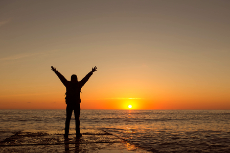 Person rejoices at a better sunrise on a beautiful coast.