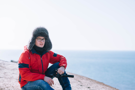 A young guy in glasses sits on top of a mountain above the sea with a phone.