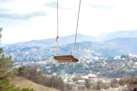 Swing in the mountains and in the forest with a picturesque view of the city.