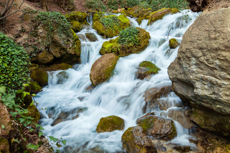 Waterfall among the stones and green plants in the spring.