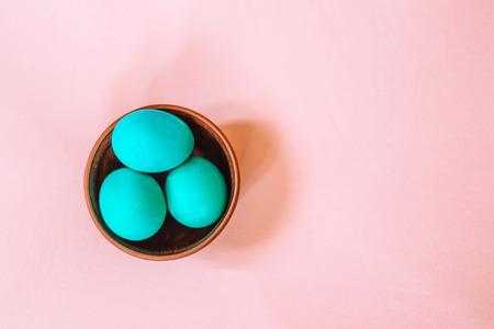 부드러운 분홍색 배경에 나무 접시에 청록색의 부활절 달걀 3개.