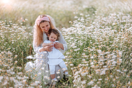 Happy family mother with cute little baby girl in daisy field.