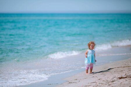 Little naughty girl dressed in a blue dress is walking along the beach.