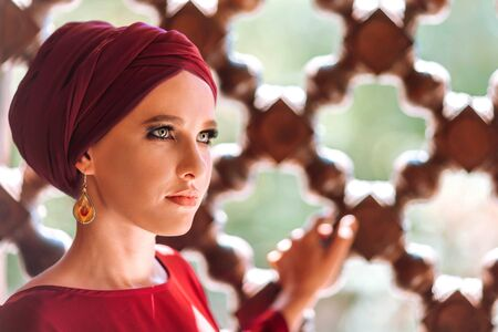 Portrait of a beautiful woman with makeup in a turban on the background. Foto de archivo