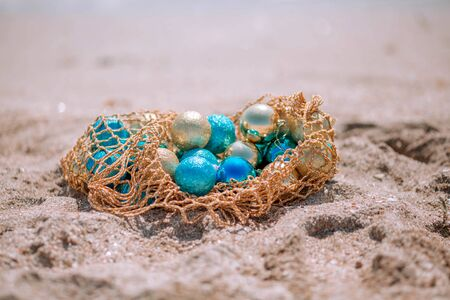Blue and gold Christmas balls in a grid on a sandy beach.