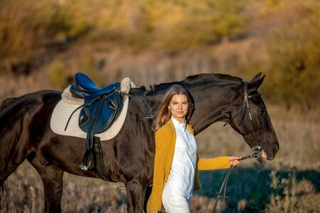 Lovely young girl hugs her horse.