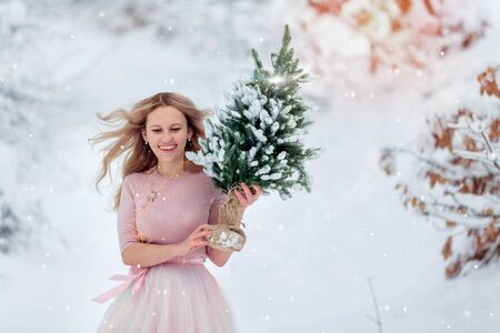 Happy woman holding a green Christmas tree on the background of snow.