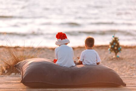 Two little boys on the beach at Christmas with a New Year tree.Christmas concept. Stock Photo