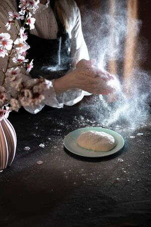 Womans hands knead the dough on the table with flour and ingredients. Banque d'images