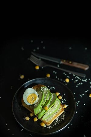 Sandwich with egg, avocado, chickpea and sesame seeds on a black background. Healthly food. Vegan concept.
