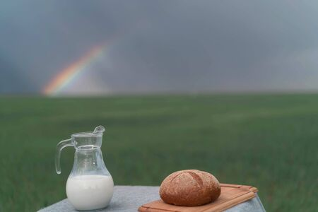 Still life with bread and milk on a table in the middle of a green field and blue sky. Foto de archivo