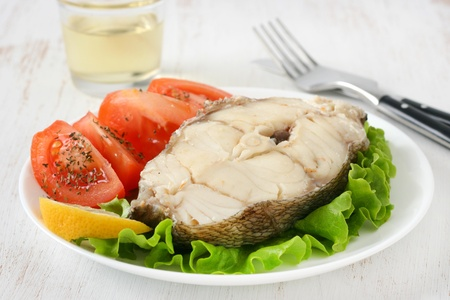 boiled fish with glass of wine photo