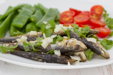 fried sardines with boiled green beans and tomato photo