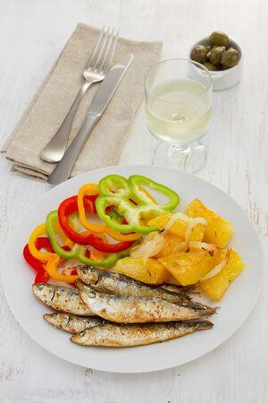 sardinas: sardinas fritos con patatas y una copa de vino Foto de archivo