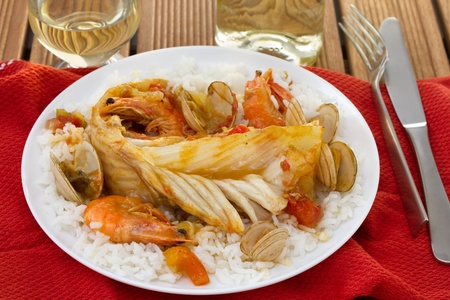 fish with seafood and rice on the plate photo