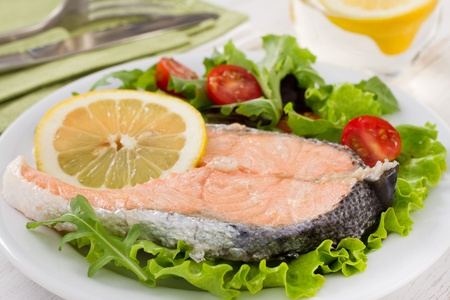 boiled salmon with lemon on the white plate photo