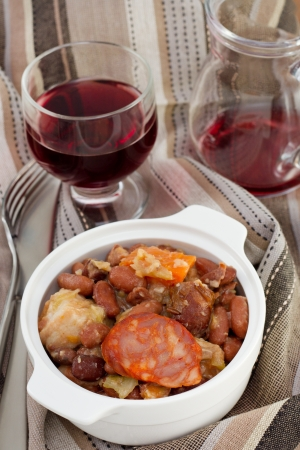 sausages and beans stew with glass of wine photo