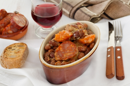 sausages and meat with red beans and glass of red wine photo