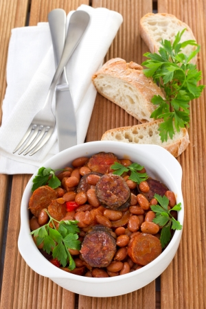 beans with sausages and sauce in the white bowl Stock Photo