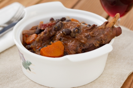 rabbit stew in the white bowl with glass of wine photo