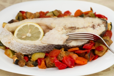 boiled fish with vegetables and lemon photo