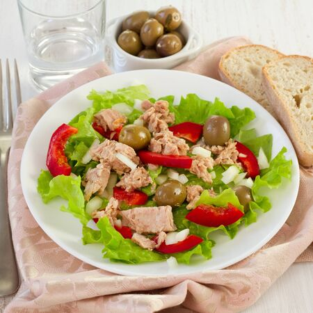 tuna salad on the plate and olives in the bowl