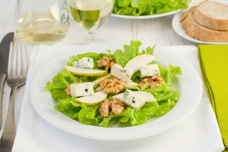 salad with gorgonzola, pear and walnut in the white plate photo