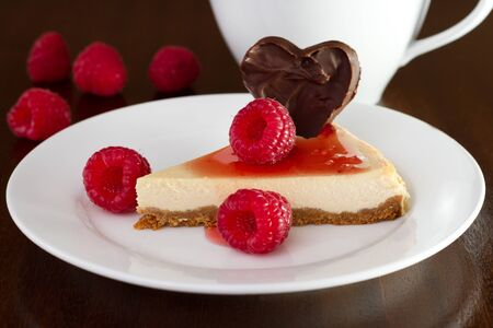 cheesecake with raspberries and cup of tea photo