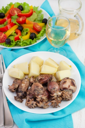 fried cuttlefish with boiled potato on the plate and salad
