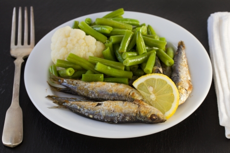 fried sardines with vegetables and lemon photo