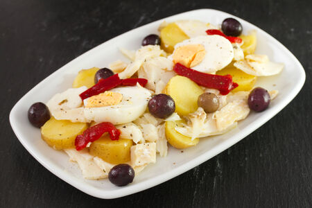 cod fish salad with olives in white dish