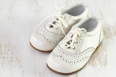 white baby shoes on white wooden background photo