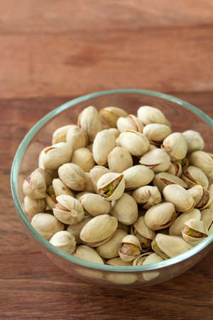 pistachios: pistachios in bowl in brown wooden background Stock Photo