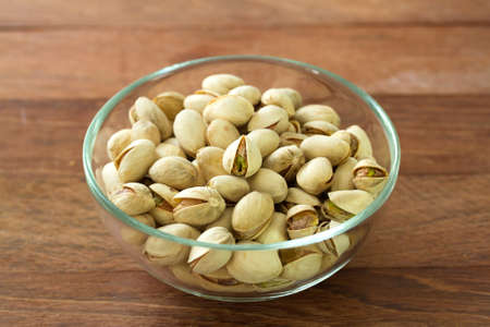 pistachios: pistachios in bowl in brown background