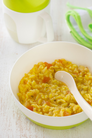 baby rice: baby food rice with vegetables and rice in bowl with spoon Stock Photo