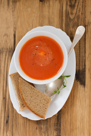 cold soup: tomato soup in white bowl with sandwich on brown background