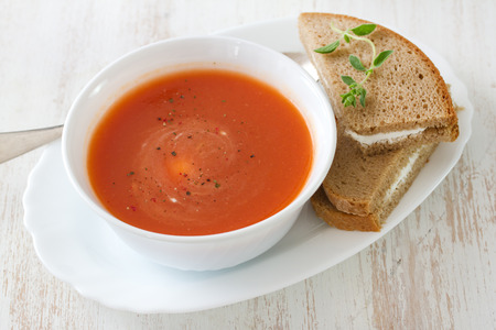 cold soup: tomato soup in white bowl with sandwich on white background