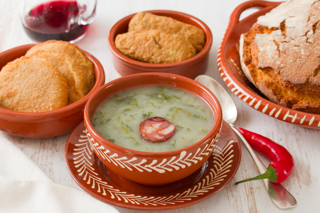 portuguese soup caldo verde in ceramic dish and spoon with corn bread and appetizers