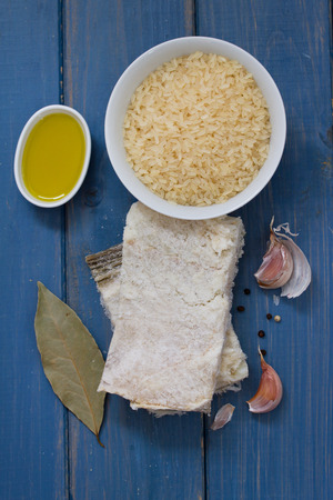codfish: codfish with rice, olive oil and garlic on blue wooden background