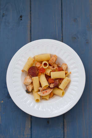 pasta with dry tomato and smoked sausages on plate