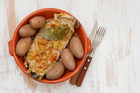 potato tuna: tuna with onion and potato in ceramic dish on white wooden background Stock Photo