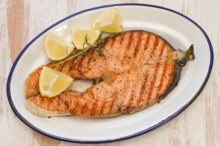gilled: grilled salmon with lemon on dish on white wooden background Stock Photo