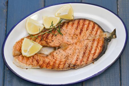 gilled: grilled salmon with lemon on dish on blue wooden background Stock Photo
