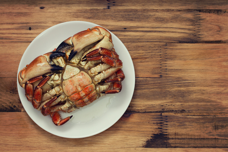 crab: boiled crab on white plate on brown background Stock Photo